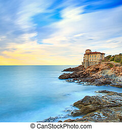 Boccale castle landmark on cliff rock and sea on sunset. Tuscany, Italy, Europe. Long exposure photography.