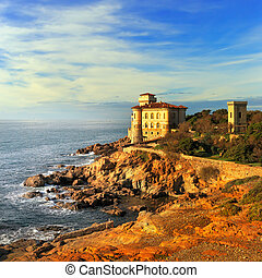 Boccale castle landmark on cliff rock and sea on warm sunset. Tuscany, Italy