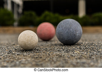 Bocce Balls on Gravel White in Focus with Red and Blue in...