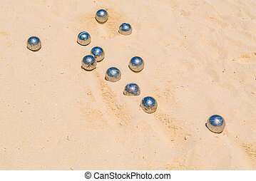 Bocce balls on white sandy beach .
