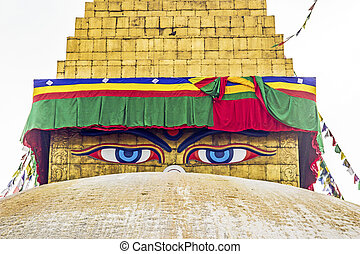 bodhnath stupa in kathmandu with buddha eyes and prayer flags with clear blue sky