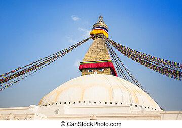 Bodhnath Stupa with buddha eyes and prayer flags, clear blue sky, Kathmandu, Nepal. Stock Photo: