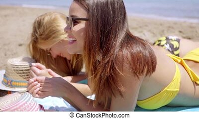 Bodies of two shapely women in bikinis lying tanning on a...