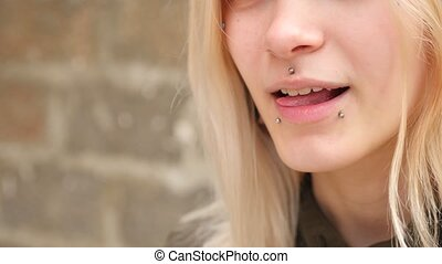 bodimodification, portrait of a girl with face piercings and...
