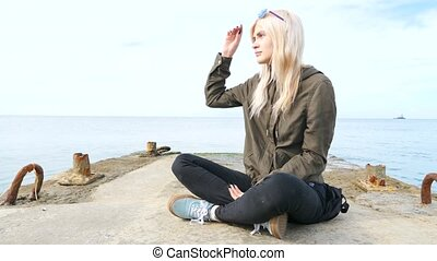 bodimodification, portrait of a girl with face piercings and tunnels in the ears. girl informal sits on the sea dock. 4k, slow-motion shooting, copying space