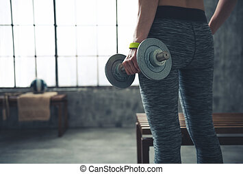 Closeup on fitness woman holding dumbbell in urban loft gym