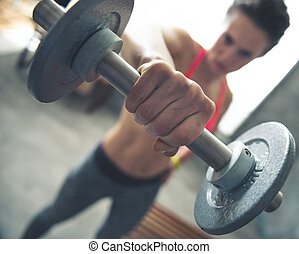Closeup on fitness woman lifting dumbbell in loft gym - Body...