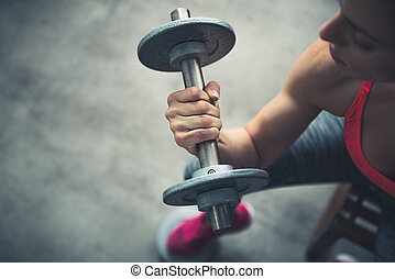Closeup on fitness woman workout with dumbbell in urban loft...