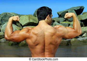body builder flexing his back by the ocean with rocks in the...