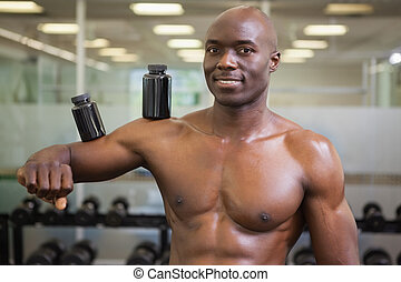 Body builder holding bottles with s