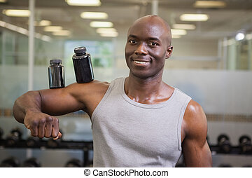 Body builder holding bottles with supplements on biceps - ...