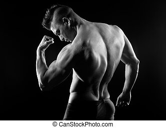 Body builder posing and showing off bicep muscle on dark...