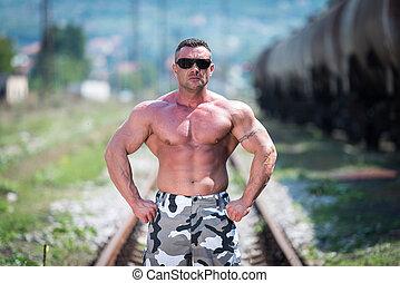 Body Builder Posing At The Railroad