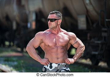 Body Builder Posing At The Railroad - Bodybuilder Showing...