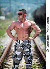 Bodybuilder Showing His Front Lat Spread Outdoors At Railroad