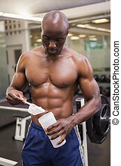 Body builder scooping up protein powder - Shirtless body ...