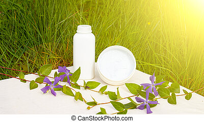 body care cosmetics in white bottles with purple wildflowers on a background of green grass in the sun, skin care, beauty, spa
