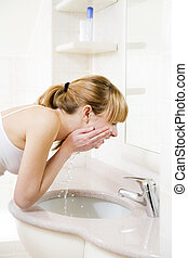body care - side profile of a young woman washing her face ...