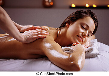 Spa body massage treatment. Woman having massage in the spa salon