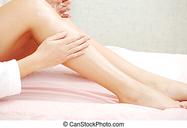 Body care. - Woman is applying cream on her legs, sitting on...