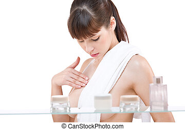Body care: Young woman applying lotion in bathroom, isolated...
