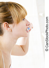 body care - Young woman looking into a mirror brushing her ...