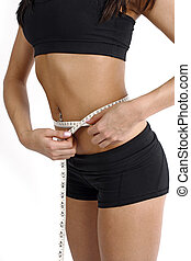 Body conscious - A tanned slim young woman measuring her ...