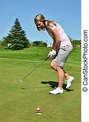 A woman golfer applies body english on a short putt
