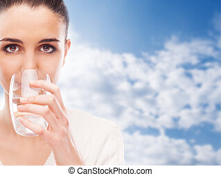 Body hydration - Young woman drinking a glass of fresh...
