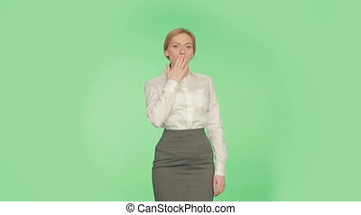Body language. Beautiful blonde girl in a skirt and a white blouse on a green background. gestures, of lies cover, her mouth