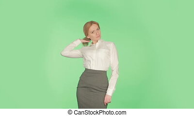 Body language. Beautiful blonde girl in a white blouse on a green background.