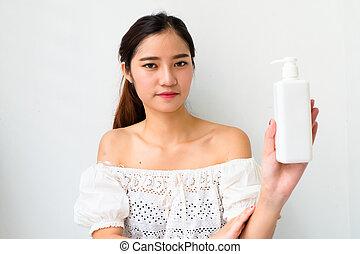 Body lotion Portrait of Beautiful Woman looking at Camera. Beautiful Asian female model on Whitebackground