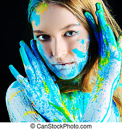 Art project: beautiful woman painted with many vivid colors. Over black background.