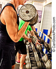 Body part of group people working with dumbbells at gym.