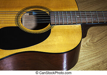 body part of yellow 12 string guitar lying on the wooden ...
