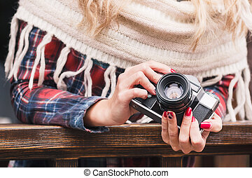 Body part: woman holds an old camera