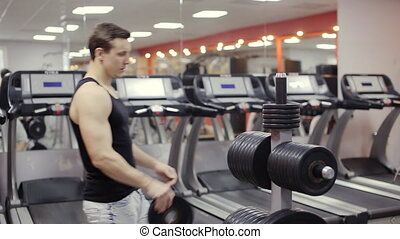 Bodybuilder change weight on  barbell in the gym