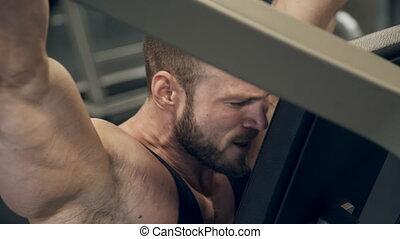 Bodybuilder clutching his teeth raises hands heavily up on...