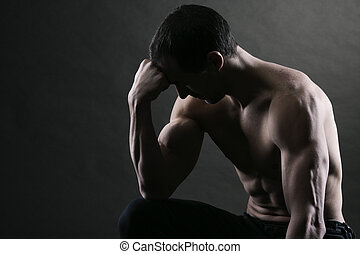 Bodybuilder concentrating on dark background