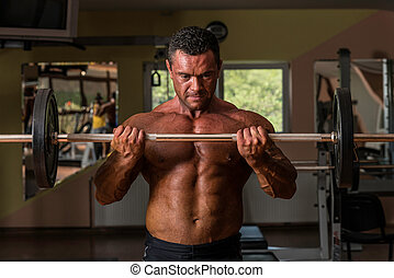bodybuilder doing heavy weight exercise for biceps with barbell