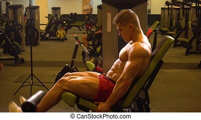 Bodybuilder doing leg exercise on machine - Bodybuilder man...
