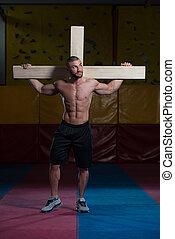 Bodybuilder Dragging a Wooden Cross