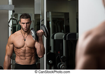 Bodybuilder Exercising Biceps With Dumbbells - Fit Athlete...