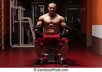 Bodybuilder Exercising Biceps With Dumbbells