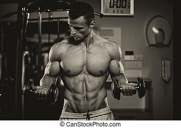 Bodybuilder Exercising Biceps With Dumbbells - Young Man...