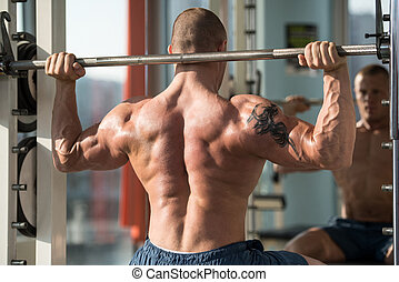 Bodybuilder Exercising Shoulders With Barbell