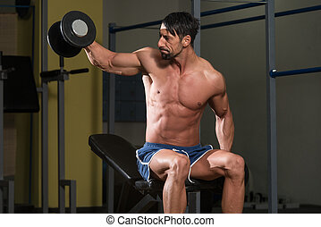 Bodybuilder Exercising Shoulders With Dumbbells
