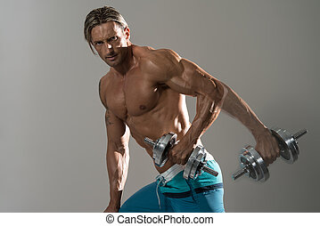 Bodybuilder Exercising Triceps With Dumbbells On Grey Background