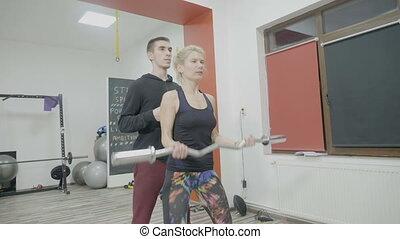 Bodybuilder female in sportswear working out with heavy...