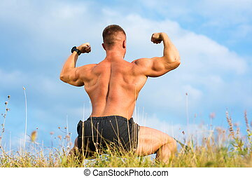 Bodybuilder flexing back muscles outdoors